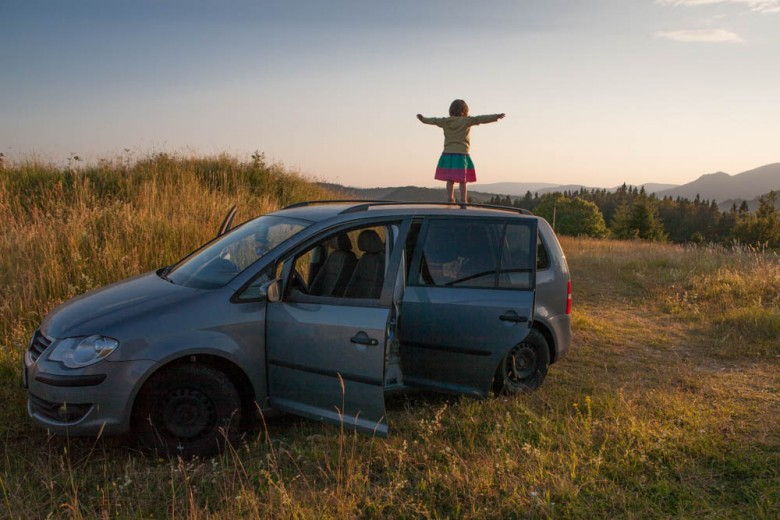 Small girl standing on a car in the sunset (Travel, Car)